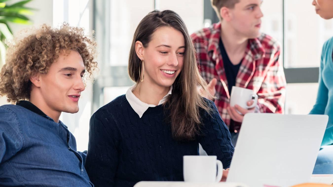 Glada människor vid dator